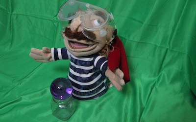 A pirate puppet with an eyepatch, safety goggles and a huge scraggly mustache watches over a purple crystal ball at his feet.'